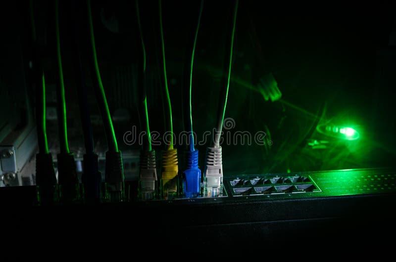 Διακόπτης δικτύων και ethernet καλώδια, σύμβολο των παγκόσμιων επικοινωνιών Χρωματισμένα καλώδια δικτύων στο σκοτεινό υπόβαθρο με στοκ εικόνα