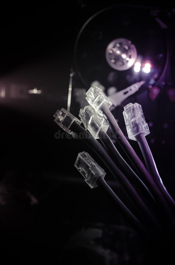 Διακόπτης δικτύων και ethernet καλώδια, σύμβολο των παγκόσμιων επικοινωνιών Χρωματισμένα καλώδια δικτύων στο σκοτεινό υπόβαθρο με στοκ φωτογραφίες