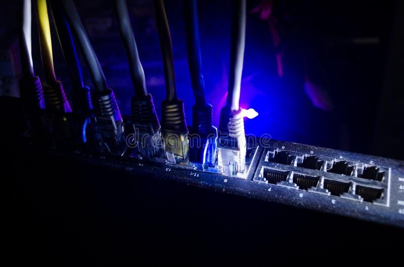 Διακόπτης δικτύων και ethernet καλώδια, σύμβολο των παγκόσμιων επικοινωνιών Χρωματισμένα καλώδια δικτύων στο σκοτεινό υπόβαθρο με στοκ εικόνες