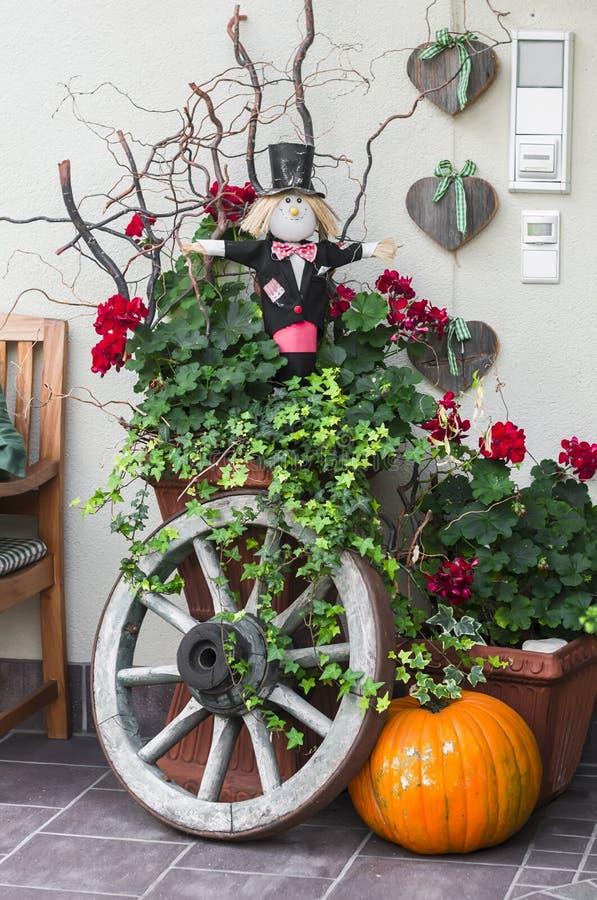 Διακόσμηση αποκριών - κολοκύθα, σκιάχτρο, παλαιά ξύλινη ρόδα κοντά στην πόρτα στοκ φωτογραφία