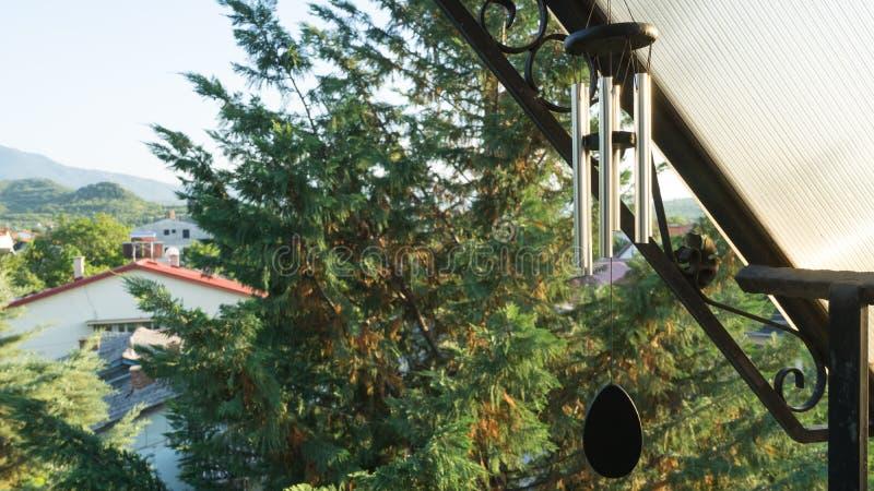 Διακόσμηση κήπων, κτύποι αέρα που κρεμά κάτω από τη στέγη του μπαλκονιού ενός σπιτιού Δέντρο κυπαρισσιών στην οδό μιας γειτονιάς  στοκ εικόνα με δικαίωμα ελεύθερης χρήσης