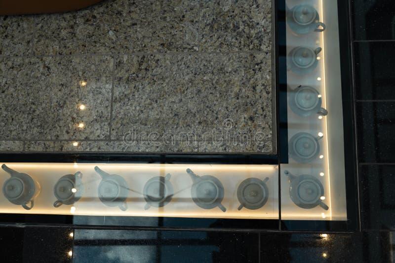 Διακόσμηση λεωφόρων αγορών - δοχεία τσαγιού κάτω από ένα πάτωμα γυαλιο στοκ εικόνες