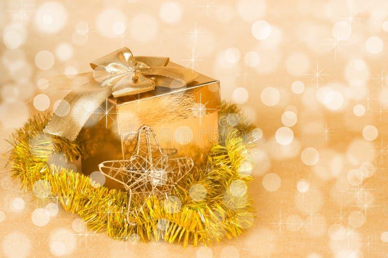 Διακόσμηση Χριστουγέννων και κιβώτιο δώρων σε ένα χρυσό bokeh στοκ φωτογραφία
