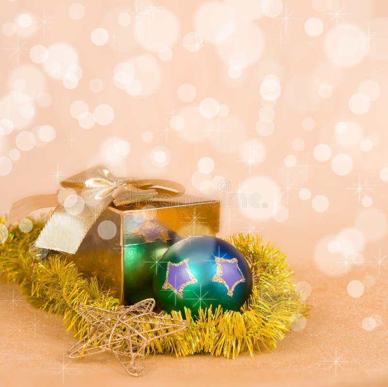 Διακόσμηση Χριστουγέννων και κιβώτιο δώρων σε ένα χρυσό bokeh στοκ εικόνα με δικαίωμα ελεύθερης χρήσης