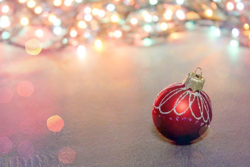 Διακόσμηση Χριστουγέννων, κόκκινη σφαίρα σε ένα κενό υπόβαθρο για το κείμενο, bokeh στοκ εικόνα