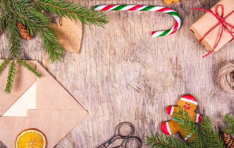 Διακόσμηση Χριστουγέννων με ένα δέντρο, ένα κομψό, άτομο μελοψωμάτων, ένα δώρο, έναν φάκελο, έναν κάλαμο καραμελών και ένα ψαλίδι στοκ φωτογραφία με δικαίωμα ελεύθερης χρήσης