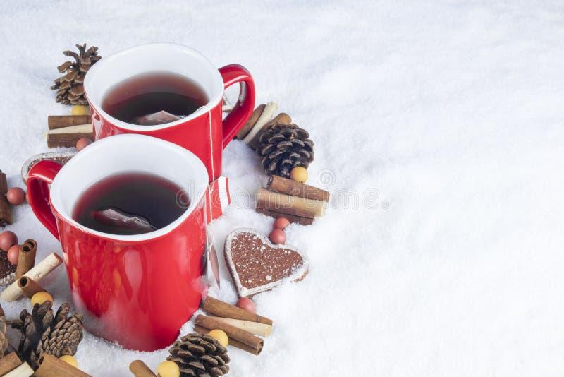 Διακόσμηση Χριστουγέννων με δύο κόκκινα φλυτζάνια του καυτού τσαγιού σε ένα backgroun στοκ εικόνα με δικαίωμα ελεύθερης χρήσης
