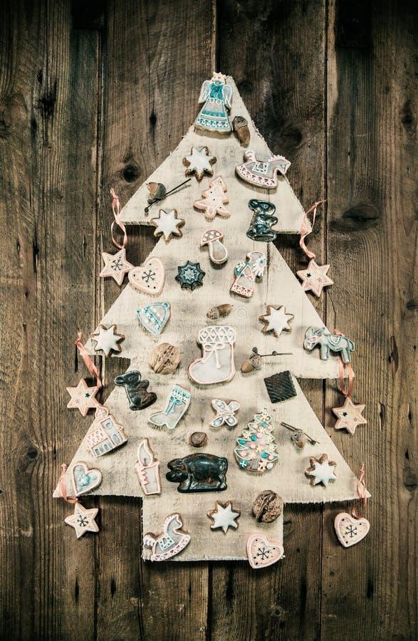 Διακόσμηση Χριστουγέννων: ξύλινο χαρασμένο δέντρο που διακοσμείται με το gingerbr στοκ εικόνες