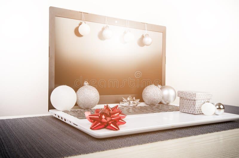 Διακόσμηση Χριστουγέννων σε έναν υπολογιστή Lap-top σε έναν ξύλινο πίνακα και έναν άσπρο τοίχο Επιχειρησιακή έννοια κατά τη διάρκ στοκ φωτογραφία