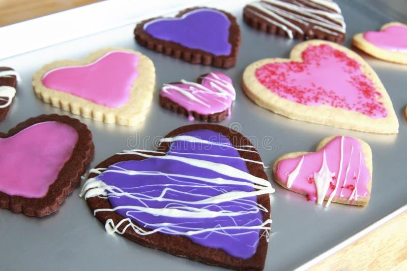 Διαμορφωμένα καρδιά μπισκότα βανίλιας και σοκολάτας με τη ρόδινη και πορφυρή τήξη στοκ φωτογραφία