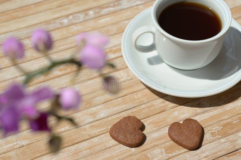 Διαμορφωμένα καρδιά σοκολάτας λουλούδια ορχιδεών καφέ μπισκότων μαύρα στοκ φωτογραφία