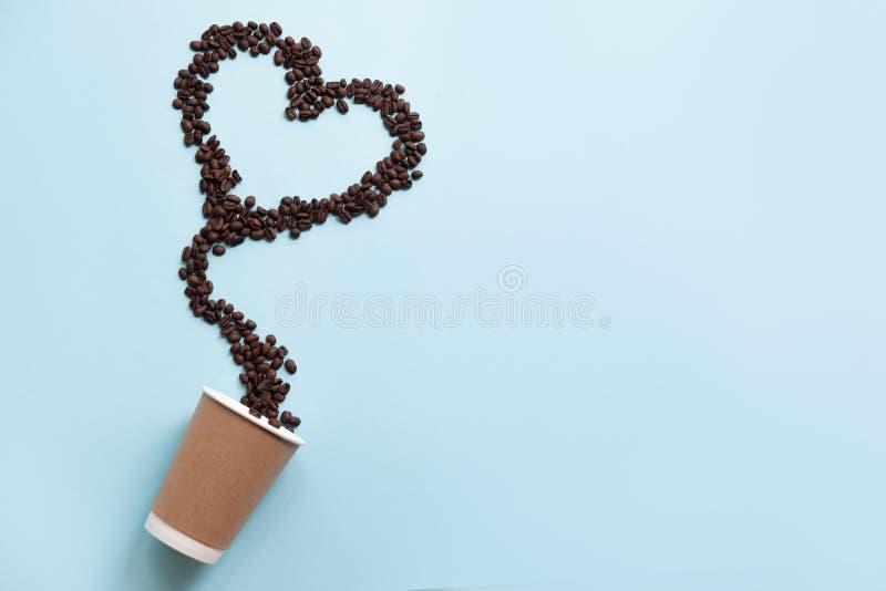 Διαμορφωμένα καρδιά φασόλια καφέ και φλυτζάνι εγγράφου που απομονώνεται στο μπλε υπόβαθρο στοκ φωτογραφίες