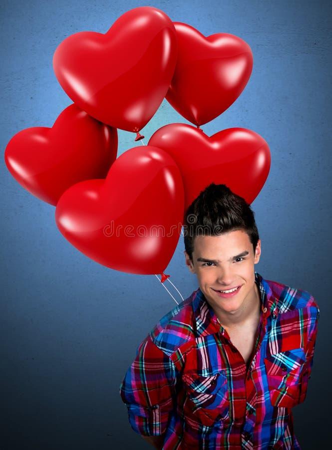 Διαμορφωμένα καρδιά μπαλόνια εκμετάλλευσης νεαρών άνδρων στοκ εικόνα