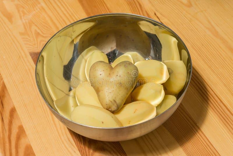 Διαμορφωμένες καρδιά πατάτες με άλλα potatos σε ένα κύπελλο στοκ εικόνες με δικαίωμα ελεύθερης χρήσης