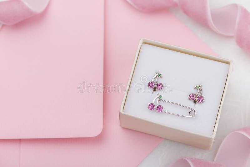 Διαμορφωμένες κεράσι σκουλαρίκια και πόρπη καρφιτσών με τα κρύσταλλα στο κιβώτιο δώρων στοκ εικόνα