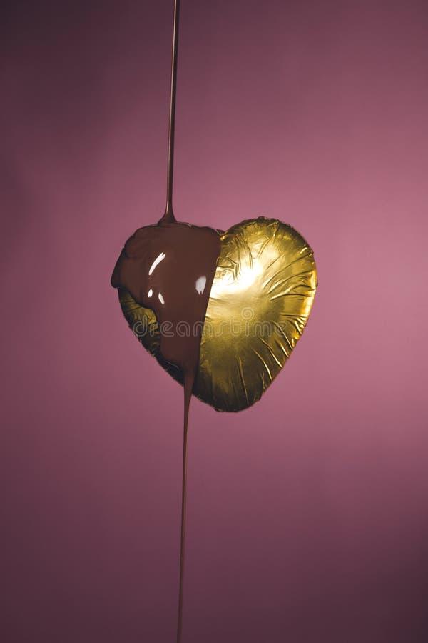 διαμορφωμένη καρδιά καραμέλα στο χρυσό περιτύλιγμα με την υγρή σοκολάτα στοκ εικόνα