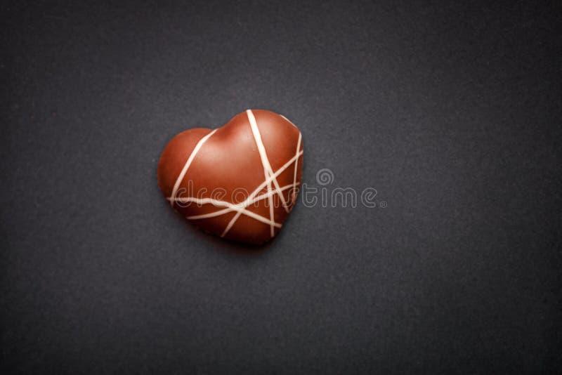 Διαμορφωμένη καρδιά πραλίνα στο σκοτεινό υπόβαθρο στοκ φωτογραφίες