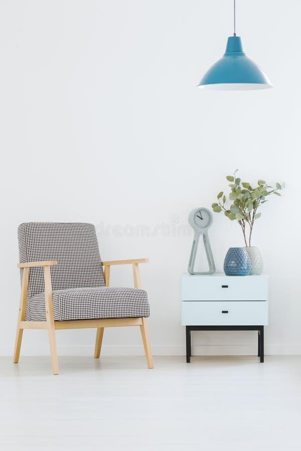 Διαμορφωμένη πολυθρόνα που στέκεται δίπλα στο μικρό ντουλάπι με το ρολόι στοκ φωτογραφία με δικαίωμα ελεύθερης χρήσης