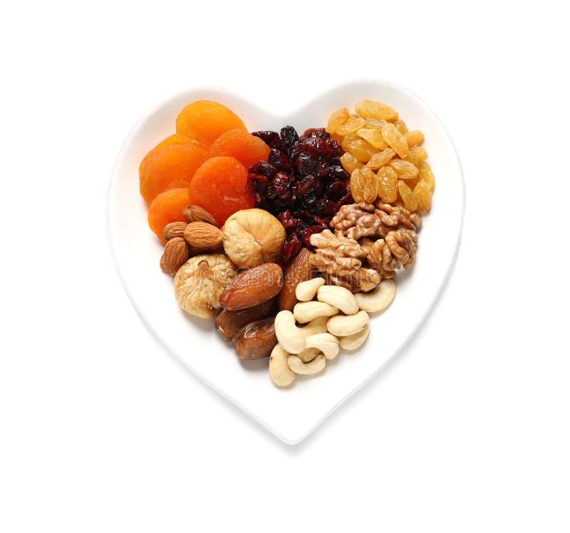 Διαμορφωμένο καρδιά πιάτο με τους διαφορετικούς ξηρούς καρπούς και τα καρύδια στο άσπρο υπόβαθρο στοκ φωτογραφίες