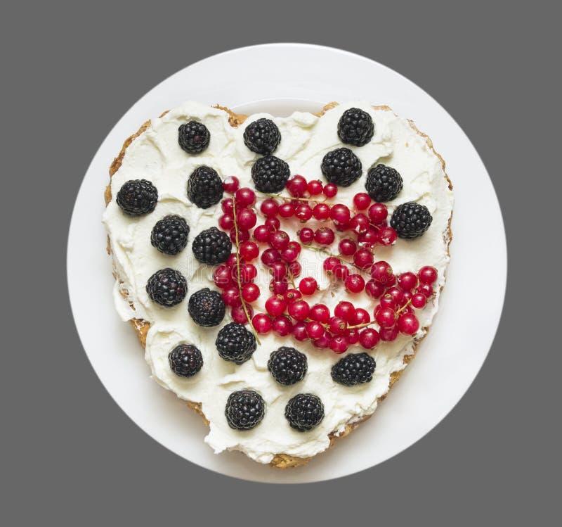 Διαμορφωμένο καρδιά κέικ με την κτυπημένα κρέμα και τα μούρα στοκ φωτογραφία