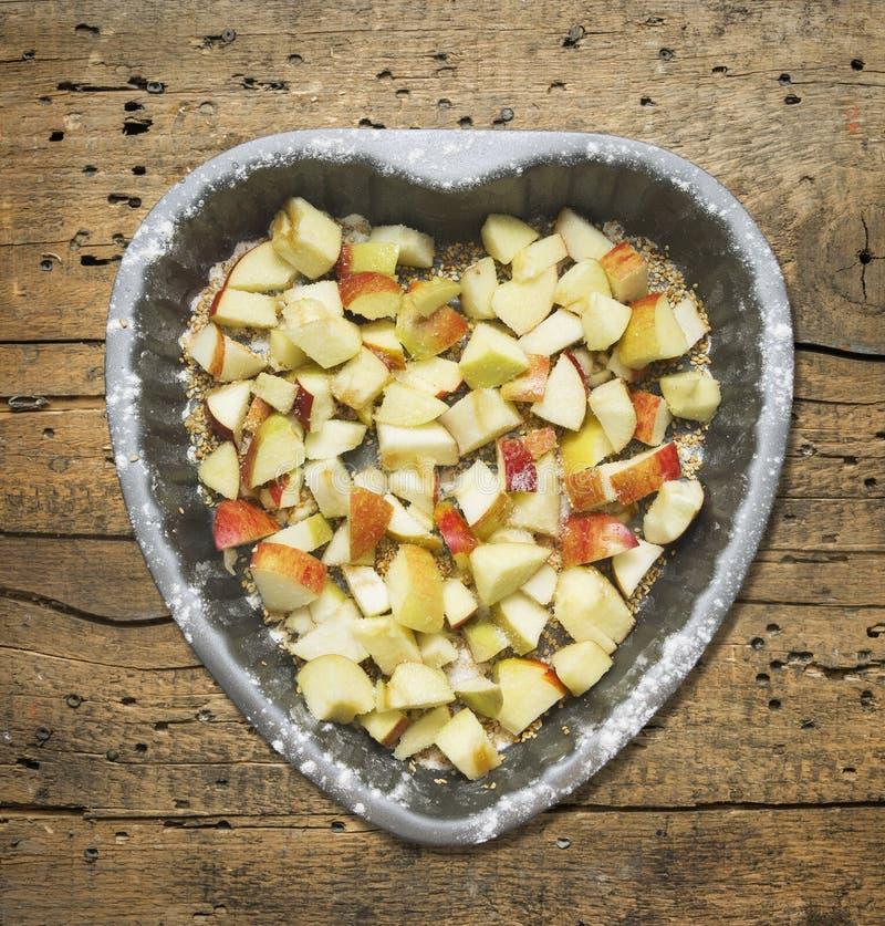 Διαμορφωμένο καρδιά κέικ με το μήλο στο παλαιό ξύλο στοκ εικόνες