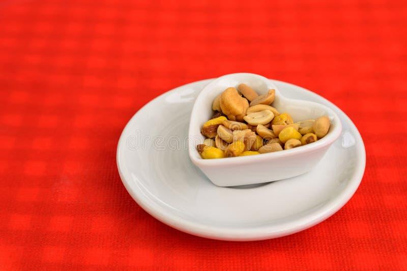 Διαμορφωμένο καρδιά κύπελλο με τα ξηρά σκληρά φρούτα και τα φυστίκια στοκ φωτογραφίες με δικαίωμα ελεύθερης χρήσης