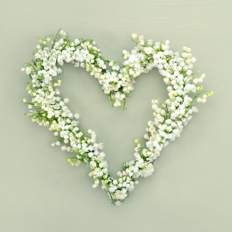 Διαμορφωμένο καρδιά στεφάνι λουλουδιών στο πράσινο υπόβαθρο στοκ φωτογραφίες
