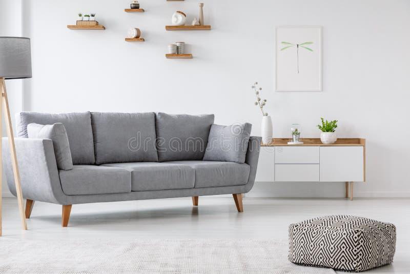 Διαμορφωμένο μαξιλάρι πουφ και γκρίζος καναπές στα ελάχιστα εσωτερικά WI καθιστικών στοκ εικόνα με δικαίωμα ελεύθερης χρήσης