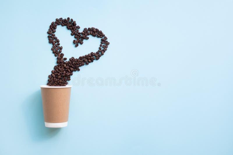 Διαμορφωμένο σύμβολο καρδιών φασολιών καφέ επάνω από το φλυτζάνι εγγράφου r στοκ φωτογραφία με δικαίωμα ελεύθερης χρήσης