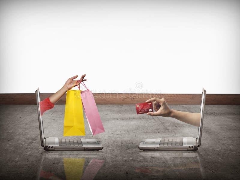 Διανείμετε από τον υπολογιστή φέρνει την τσάντα αγορών, άλλος παρουσιάζει πιστωτική κάρτα στοκ φωτογραφία με δικαίωμα ελεύθερης χρήσης