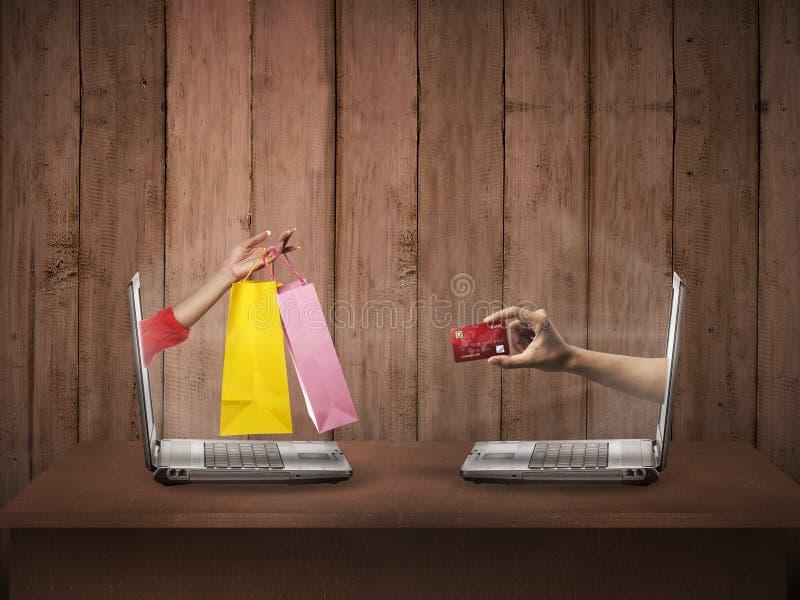 Διανείμετε από τον υπολογιστή φέρνει την τσάντα αγορών, άλλος παρουσιάζει πιστωτική κάρτα στοκ εικόνες με δικαίωμα ελεύθερης χρήσης