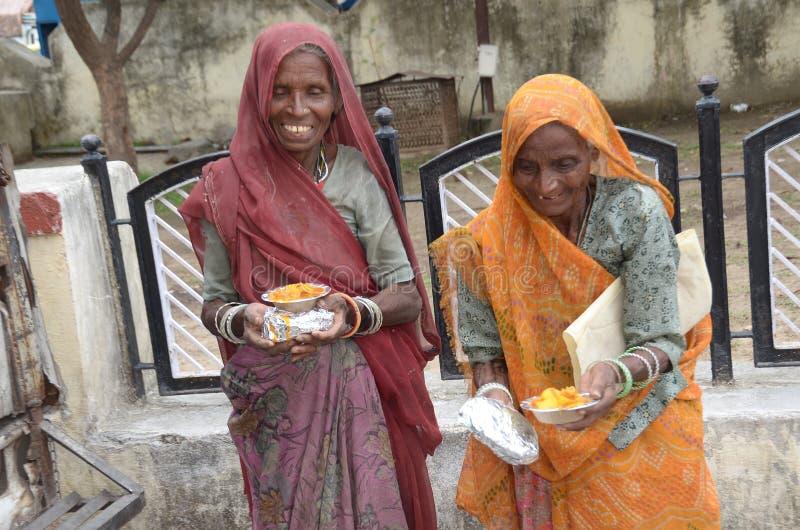 Διανείμετε τα τρόφιμα για των φτωχών γυναικών στοκ εικόνες