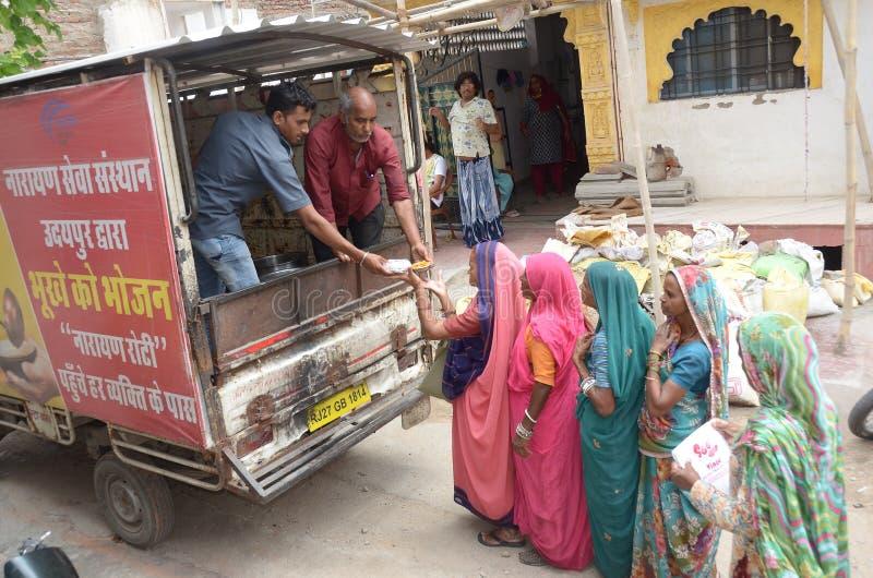 Διανείμετε τα τρόφιμα για των φτωχών γυναικών στοκ φωτογραφία