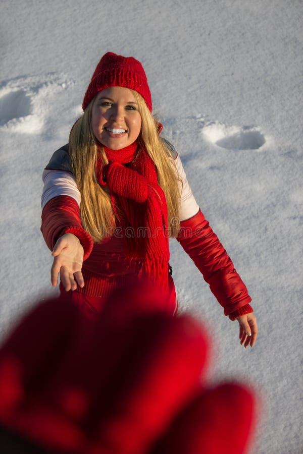 διανείμετε την επίτευξη της χαμογελώντας χειμερινής γυναίκας στοκ φωτογραφία με δικαίωμα ελεύθερης χρήσης