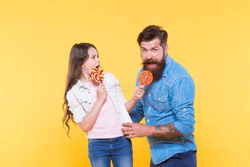 Διανομή των γλυκών με τους πιό αγαπητούς ανθρώπους Η κόρη και ο πατέρας τρώνε τις γλυκές καραμέλες E Γενειοφόρος καλός μπαμπάς hi στοκ εικόνες