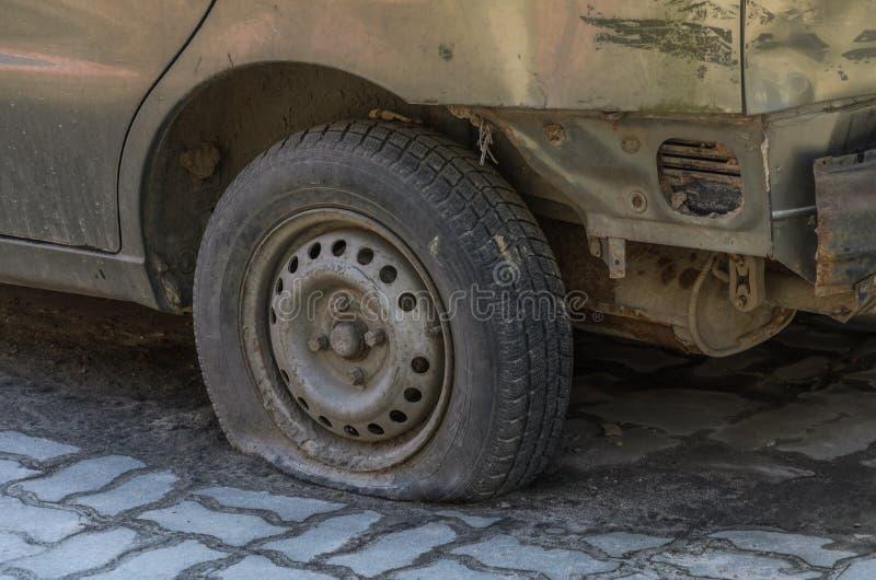 Διαπερασμένη επίπεδη ρόδα σε ένα παλαιό εγκαταλειμμένο σκουριασμένο αυτοκίνητο στοκ φωτογραφία με δικαίωμα ελεύθερης χρήσης