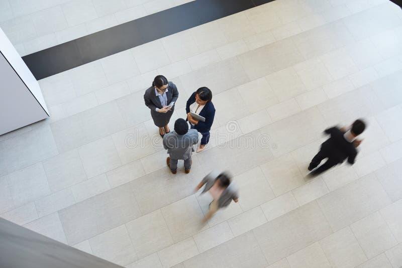 Διαπολιτισμικοί συνάδελφοι που κουβεντιάζουν κατά τη διάρκεια του σπασίματος στοκ φωτογραφίες