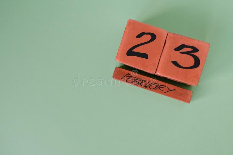 Διαρκές ξύλινο ημερολόγιο με την ημερομηνία της 23ης Φεβρουαρίου στη γωνία σε ένα πράσινο υπόβαθρο Έννοια του υπερασπιστή της ημέ στοκ εικόνες με δικαίωμα ελεύθερης χρήσης