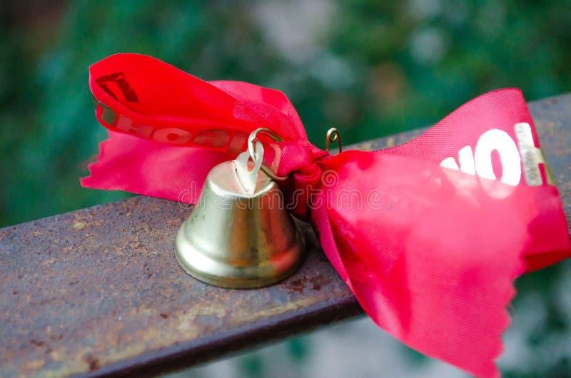 Διαρκέστε την κλήση Ένα κουδούνι με μια κόκκινη κορδέλλα o Σχολικά έτη Βαθμολόγηση Σχολικά κουδούνια στο υπόβαθρο πράσινου στοκ φωτογραφίες με δικαίωμα ελεύθερης χρήσης