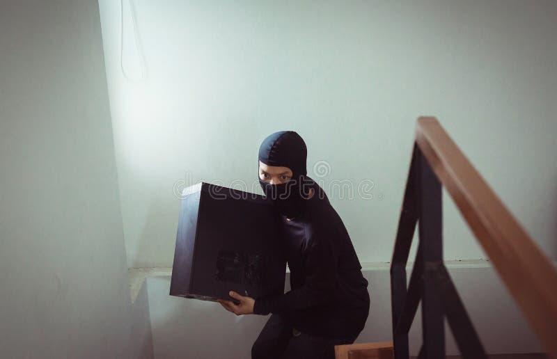 Διαρρήκτης ατόμων στο μαύρο stealing υπολογιστή ληστών μασκών από το σπίτι στοκ εικόνες με δικαίωμα ελεύθερης χρήσης