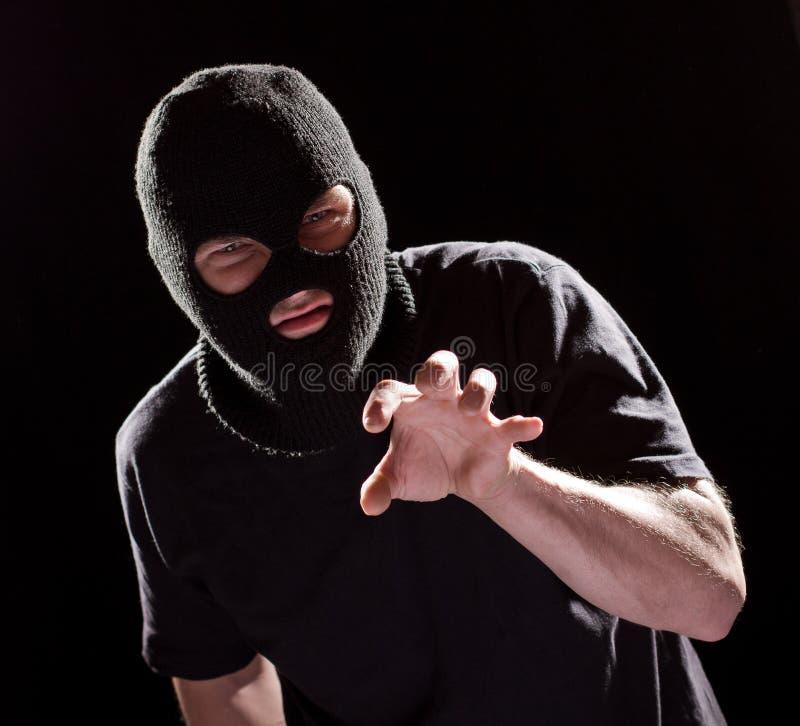Διαρρήκτης κλεφτών στην αρπαγή μασκών με το χέρι Άτομο εγκλήματος στο Μαύρο στοκ φωτογραφία με δικαίωμα ελεύθερης χρήσης
