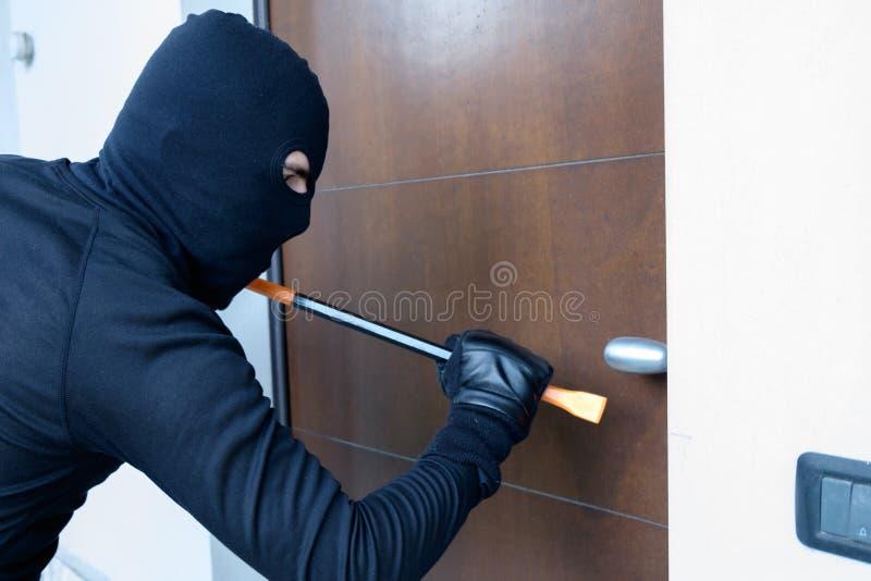 Διαρρήκτης που προσπαθεί να αναγκάσει μια κλειδαριά πορτών που χρησιμοποιεί έναν λοστό στοκ εικόνες