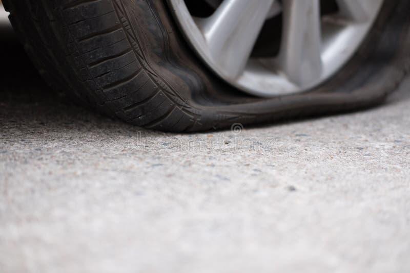 Διαρροή ροδών αυτοκινήτων λόγω του σφυροκοπήματος καρφιών επίπεδο ελαστικό αυτοκινήτου στο δρόμο flatt στοκ φωτογραφία