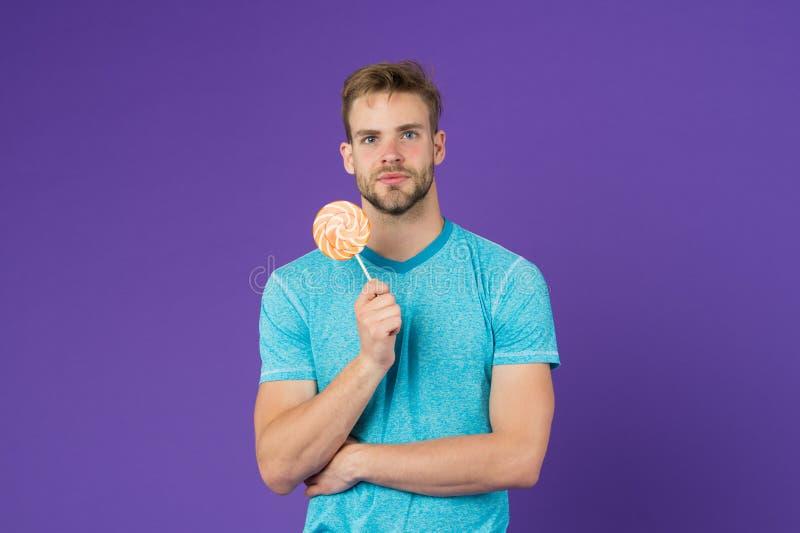 Διασκέδαση Lollipop Το άτομο τρώει το μεγάλο ζωηρόχρωμο γλυκό lollipop Το άτομο με τη σκληρή τρίχα συμπαθεί lollipop Εξαπατήστε τ στοκ εικόνα με δικαίωμα ελεύθερης χρήσης