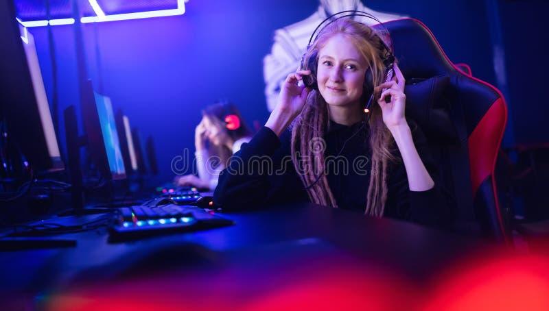 Διασκεδάστε με τις όμορφες κοπέλες που παίζουν παιχνίδια στον υπολογιστή με τα ακουστικά στοκ εικόνα
