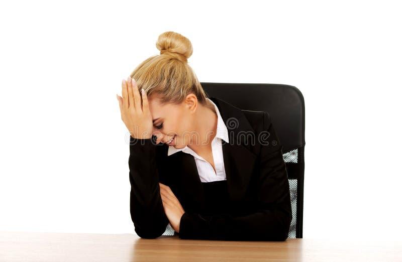Διασκεδασμένη επιχειρηματίας πίσω από το γραφείο στοκ φωτογραφία με δικαίωμα ελεύθερης χρήσης