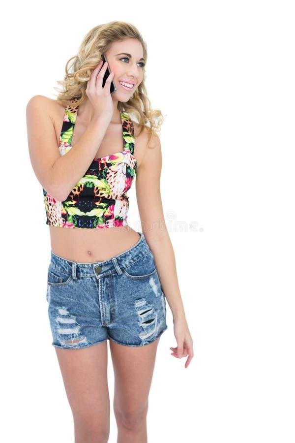 Διασκεδασμένο αναδρομικό ξανθό πρότυπο που καλεί με το κινητό τηλέφωνό της στοκ εικόνα με δικαίωμα ελεύθερης χρήσης