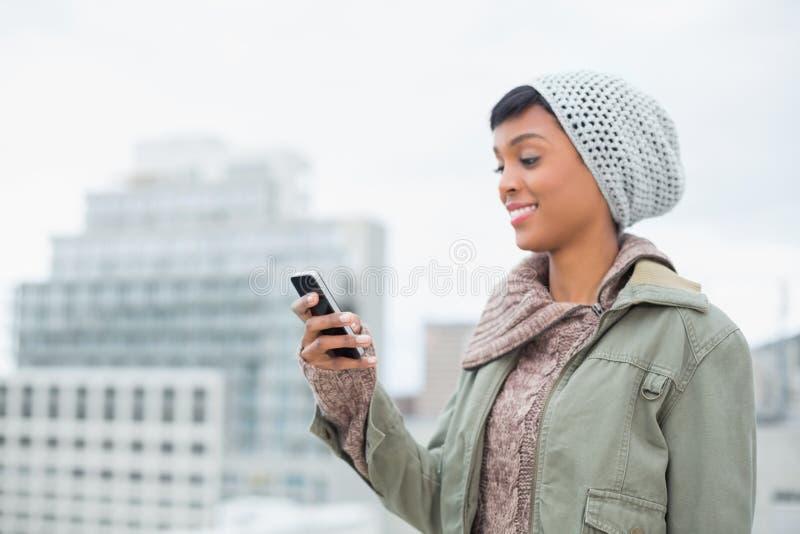 Διασκεδασμένο νέο πρότυπο στα χειμερινά ενδύματα που εξετάζουν το κινητό τηλέφωνό της στοκ εικόνα