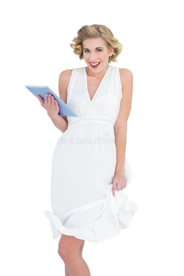 Διασκεδασμένο ξανθό πρότυπο μόδας που κρατά ένα PC ταμπλετών στοκ εικόνα