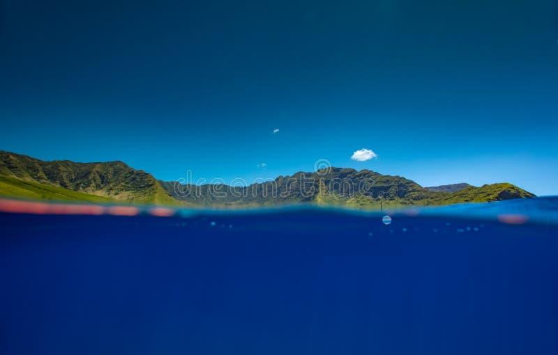Διασπασμένος πυροβολισμός του μπλε νερού και των πράσινων βουνών στοκ φωτογραφίες